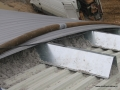 Izolacja ekofiber widoczna pomiędzy blachami dachu hali