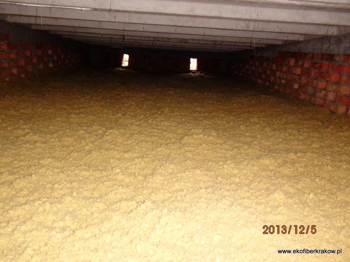 Gotowa warstwa ocieplenie stropodachu granulatem z wełny mineralnej z widocznymi kratkami wentylacyjnymi